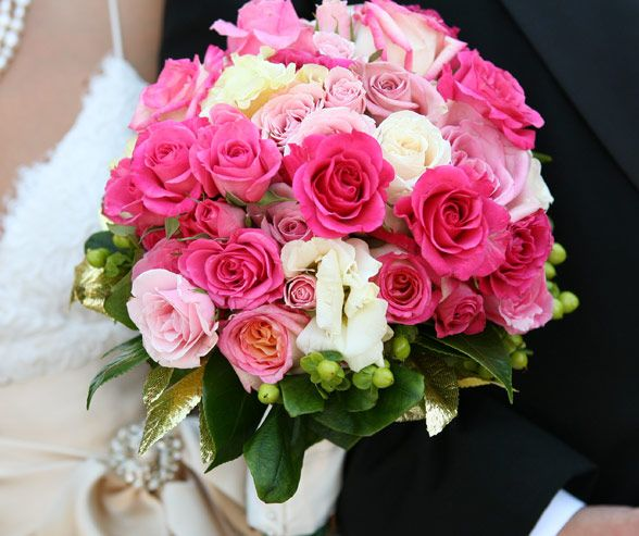 White, light pink and hot pink roses, accented with gilded leaves, make up a sweet, feminine bouquet.
