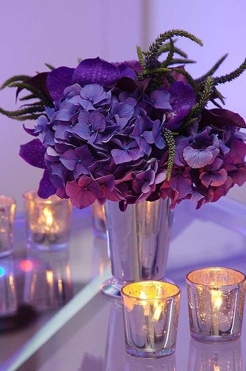 """""""A silver bud vase overflows with purple hydrangeas and orchids"""" • photo: Colin Miller on Colin Cowie Weddings"""