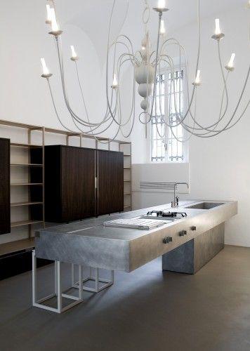 reforma cocina en vivienda rehabilitada con isla central de acero inoxidable, mueble con armarios y estanterías, suelo de microcemento.