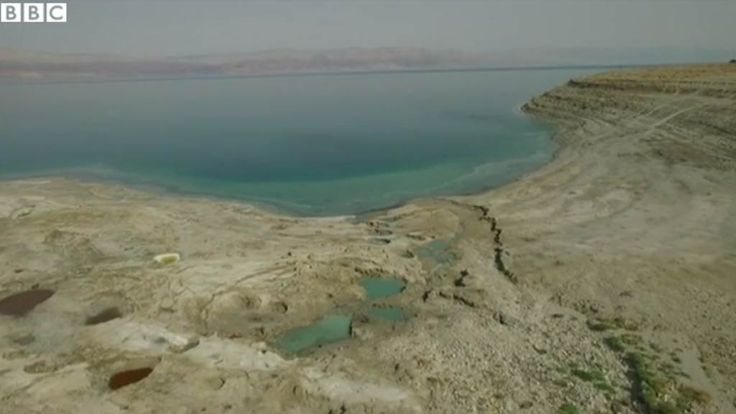 A BBC drone has taken flight to reveal how dramatically the Dead Sea is drying up and vanishing, with the retreating water mass opening up large sinkholes that have swallowed a holiday resort and a gas station.