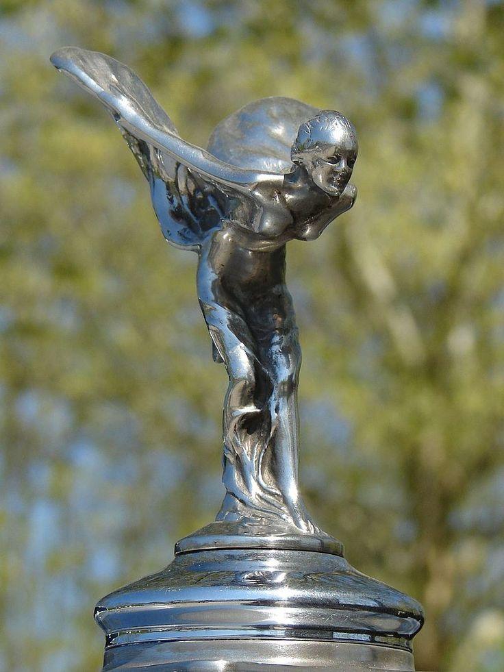"""Espírito do Êxtase em um Silver Cloud 1957. O Espírito do Êxtase (Spirit of Ecstasy, em inglês) é o principal símbolo da Rolls-Royce, presente na extremidade do capô de todos os seus carros desde 1911.[1] O êxtase é representado como uma estatueta feminina inclinada prestes a alçar voo. Apesar do """"Espírito do Êxtase"""" ser o símbolo mais reconhecido entre marcas de automóveis, o logotipo oficial da empresa são as letras """"RR"""" entrelaçadas."""