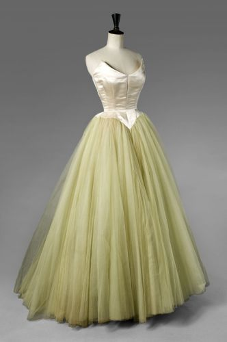 Balenciaga EISA haute couture evening dress, circa 1953. Ballgown made from duchess satin in strapless design champagne color with a rounded cutting edge appearing on each side, a reminder of the small Basque, long puff multilayer petticoat tulle silk skirt. #Cristobal Balenciaga, #EISA was named after the designer's mother, a seamstress. #House of Balenciaga. Front