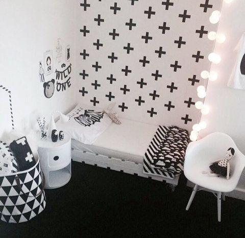 Divertido, este quarto infantil conta com estampas geométricas, brinquedos em preto e branco, e composição de quadros, varal de letras e espelho acima da cama.