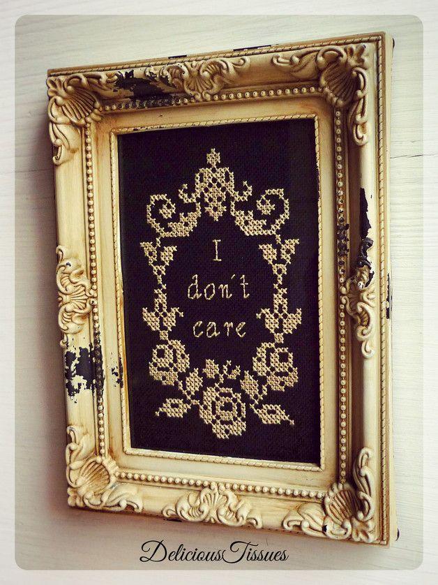 """Der in beige gestickte Schriftzug """"**I don´t care**"""" samt opulenter Rahmung wurde in traditioneller Art von Hand auf kostbare, schwarze Baumwolle gebracht und wird im antik/beigen BarockRahmen..."""