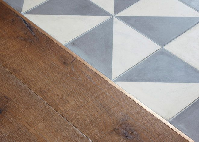 Grey and white geometric tile against dark brown floors, separated by a delicate gold line. Click through for more images of this 1800s London home.