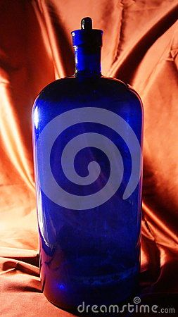 Large Antique cobalt blue apothecary bottle with back-lighting. photographed against a gold satin background. Used as an old medicine bottle used by chemists and drug dispensaries.