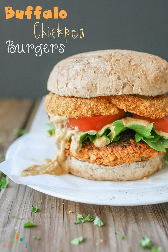 Buffalo chickpea burger topped with baked cornmeal and pepita crusted onion rings and pistachio buffalo cream