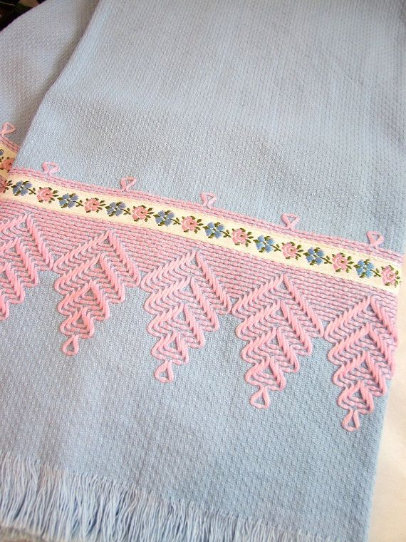 Features: Blue cotton huck toweling with swedish weaving in pink and an applied pink and blue floral trim. These towels feature swedish/huck weaving on each end and each end is fringed. Measurements: approx. 25 long x 16.5 wide Condition: Very good vintage condition - while these towels have been used, they are in wonderful condition. The towels are free from tears and obvious stains and have been recently laundered and pressed. I guess embroidered huck towels have been around for quite a…