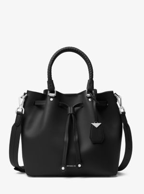 ca7f191582b0 The Blakely bucket bag is crafted from supple leather with woven top handles  for a tactile touch. Featuring a drawstring fastening and adjustable  shoulder ...