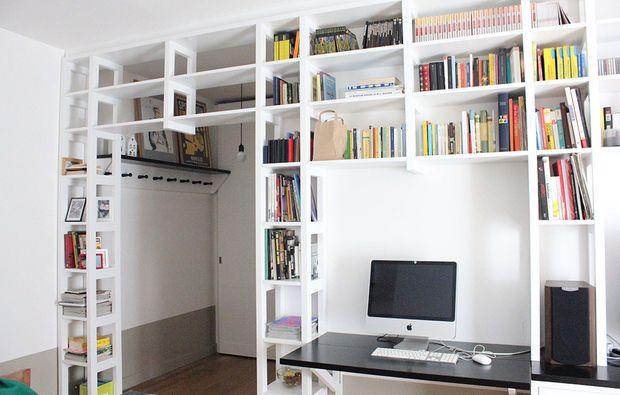 La libreria a ponte separa l'ingresso dal living e crea anche la zona TV. Casafacile.it