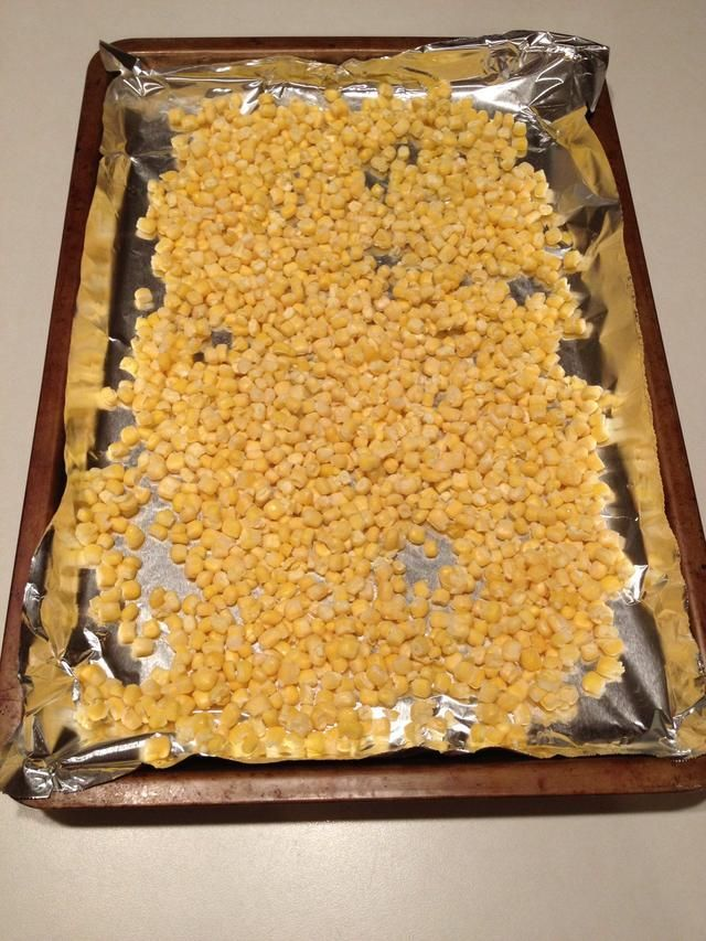 Open a bag of frozen corn and spread across the pan.