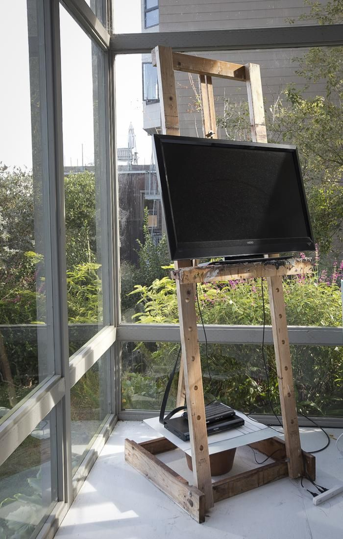 Flat screen tv displayed on artist's easel.  We have our on a rolling cart we can hide when we entertain.