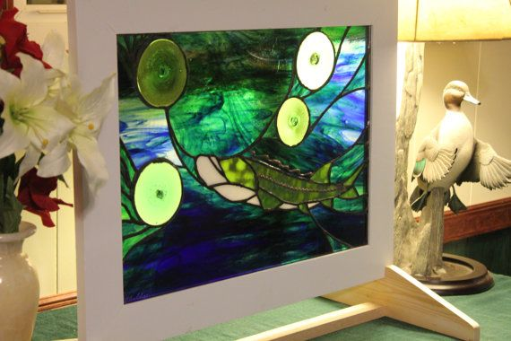 Lake Sturgeon stained glass panel. The stand makes this perfect for an apartment or an office where tenants may not be able to hang a panel in a window. The stand can be stained cherry, walnut or painted white. This is a good eye catcher to any who enter the room.