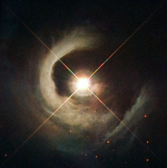 This newly released Hubble images shows the T Tauri star known as V1331 Cyg. - With its helical appearance resembling a snail's shell, this reflection nebula seems to spiral out from a luminous central star in this new NASA/ESA Hubble Space Telescope image.