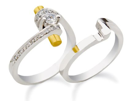 White and yellow gold engagement ring featuring a round center diamond and melee. Accompanied by a matching wedding band.