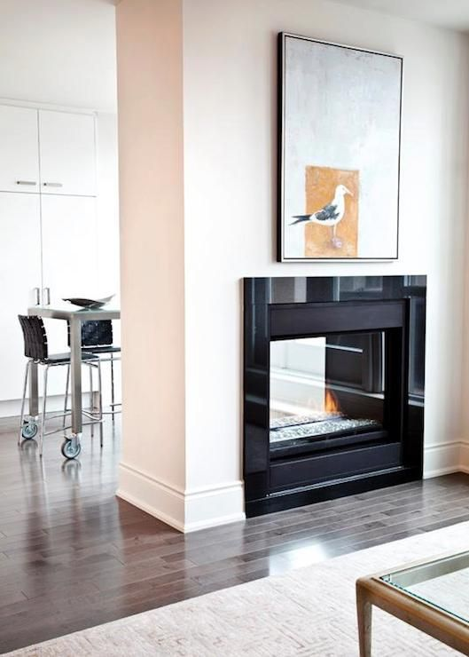 I want this double sided fireplace!!! Bright and airy living room with double sided fireplace featuring a glossy black surround with fun seagull art above. The adjoining dining room features a steel dining table on castors lined with woven black counter height stools with chrome frames.