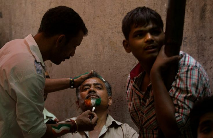 An Indian cricket fan has his beard painted in the colors of the Indian national flag, as he along with others watch on a projection screen the World Cup cricket final match between India and Sri Lanka, in New Delhi, India, Saturday, April 2, 2011. (AP Photo/Manish Swarup)