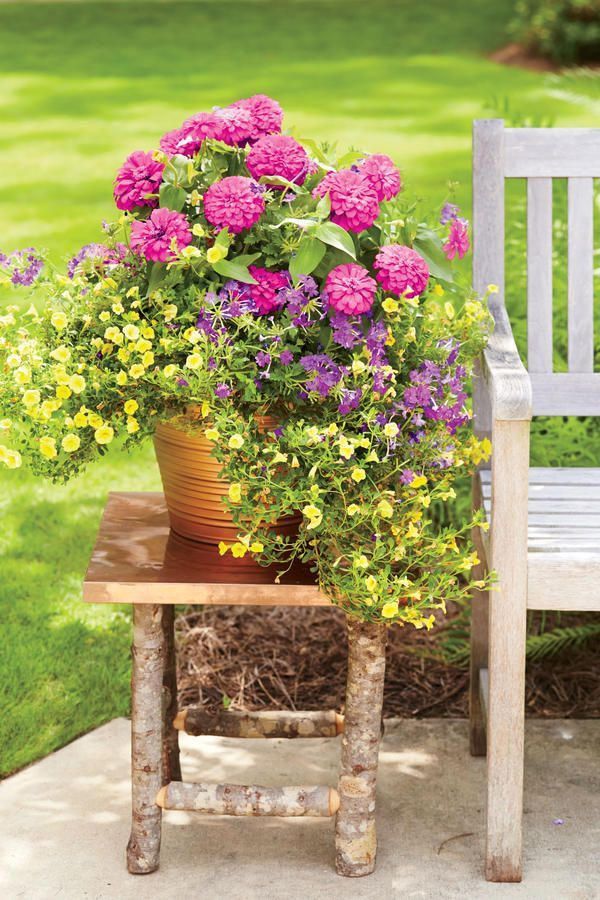 """Here's proof that a plain and simple planter has the power to brighten up a backyard side table. This container's copper sheen complements, rather than competes with, the fuchsia zinnias. The unexpected addition of yellow calibrachoas (the """"spiller"""") and purple verbenas (the""""filler"""") creates a robust focal point in an outdoor conversation space."""