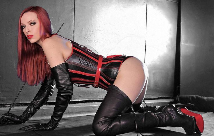 Crawling redhead in black leather gloves and boots and red and black leather corset