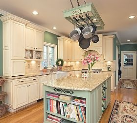 Cookery book storage on exposed side. Country French Kitchen, white painted cabinets, wood floors, granite.