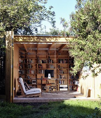 A covered wooden porch -- with built-in wooden bookshelves, of course -- makes for an outdoor reading nook you'd never have to leave!