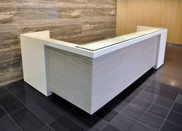 custom white and grey L shaped reception desk with floated glass transaction counter top