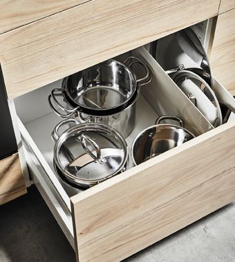 An deep kitchen drawer with an ash front that's open to show organized pots and lids