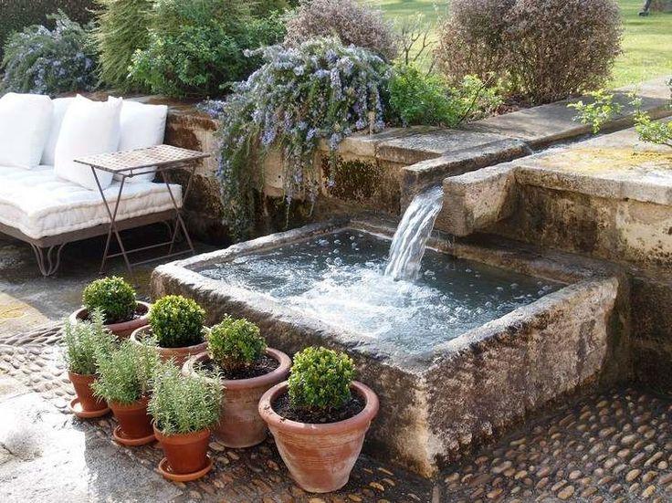 fontaine extérieure de jardin en pierre naturelle et buis en pots en terre cuite