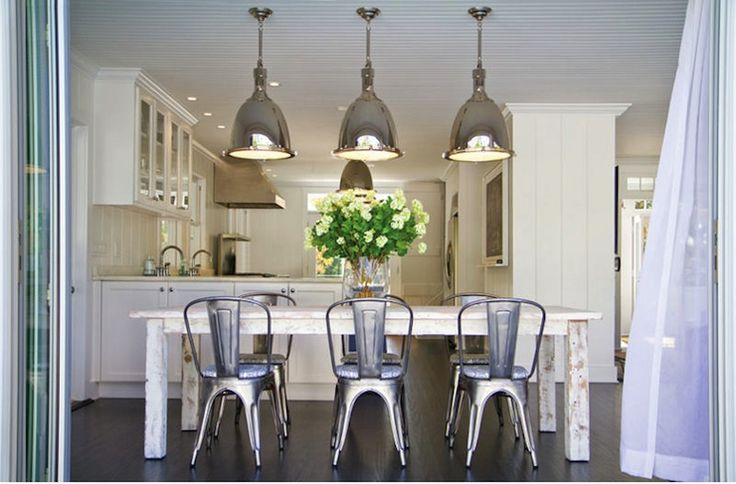 Gorgeous dining room with Restoration Hardware Benson Pendants hanging over white washed salvaged wood rectangular dining table and Crate & Barrel Lyle Side Chairs. White beadboard and dark hardwood floors in dining room.