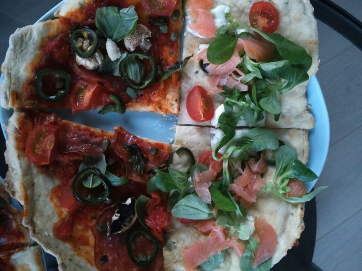 Zelfgemaakte pizza, bianco met oregano in het deeg: zalm, geitenkaas, veldsla en tomaten erop. Rossi met salami Di napoli, jalapeños, kappertjes en basilicum