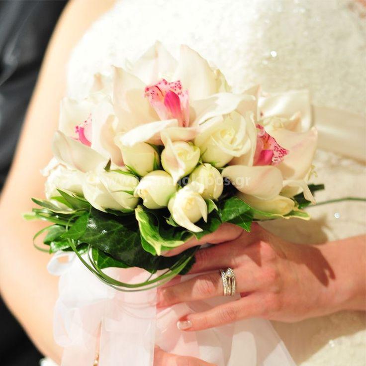 Νυφική Ανθοδέσμη Γάμου, Νυφικό μπουκέτο με ολόφρεσκα λουλούδια ιδανικό για να συμπληρώσει μια ξεχωριστή νύφη. Το πιο σημαντικό μπουκέτο της ζωής σας επιλεγμένο να συμπληρώσει ιδανικά το στυλ του γάμου που έχετε επιλέξει, από μοντέρνο σε κλασσικό ή ρομαντικό. Το πιο όμορφο στολίδι στα χέρια σας.  Μοναδικό ρομαντικό μπουκέτο με τις ιδιαίτερες ορχιδέες-συμπίτιουμ απόλυτα συνδιασμένες με το βασιλιά των λουλουδιών, το τριαντάφυλλο και διακριτικό φύλλωμα.