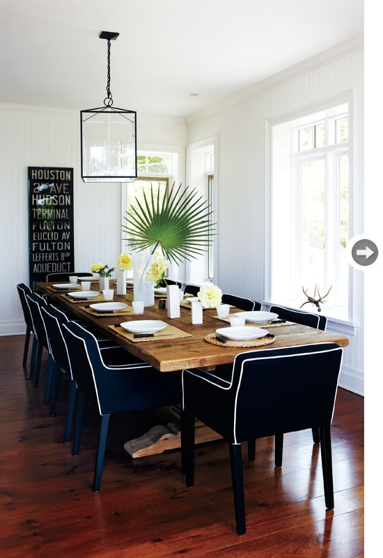 rustic reclaimed wood dining table paired with modern upholstered chairs in navy with high contrast white piping