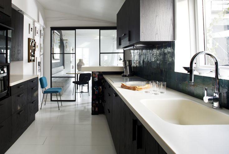 Cuisine d'un duplex parisien - Des touches de noir sur les placards pour la profondeur, de la céramique foncée pour habiller le mur le plus salissant