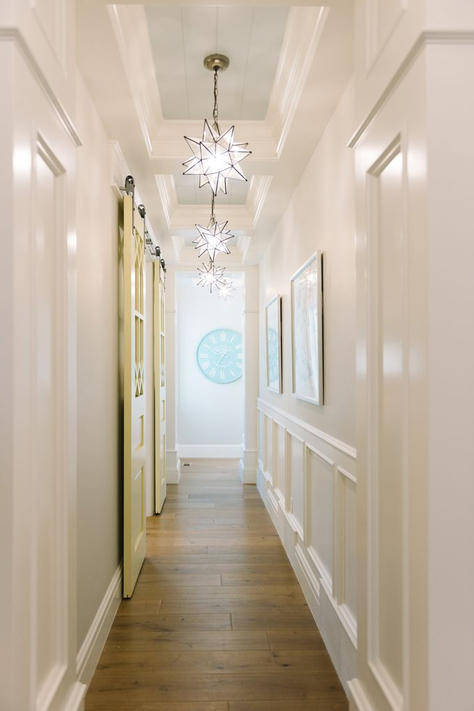 Long hallway with blue shiplap ceiling accented with moravian star pendants illuminating upper walls painted white and lower walls clad in wainscoting