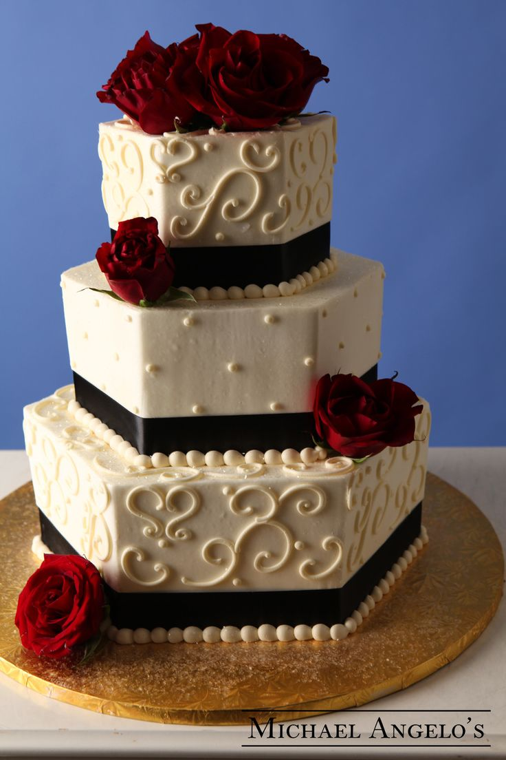 Hexagon Rose #35Classic This is a buttercream hexagon-shaped cake with the classic swirl design and ribbon surrounding the bottom of each tier. Fresh flowers were added to bring out a little color. The flowers were provided by the florist at the hall, but can also be brought in prior to the wedding