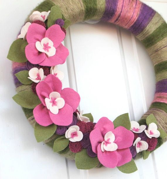 This unique and beautiful wreath features many handmade felt flowers of my own design. The vibrant pastel color scheme is perfect for welcoming