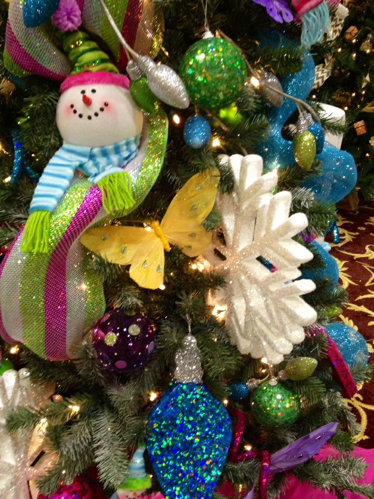 Glitter snowflakes, butterflies, light up snowmen, and sequined lightbulb ornaments from @burton + BURTON create a whimsical tree! Lots of fun and color on one tree! #christmastreedecor #whimsical #unique #ornaments #bright