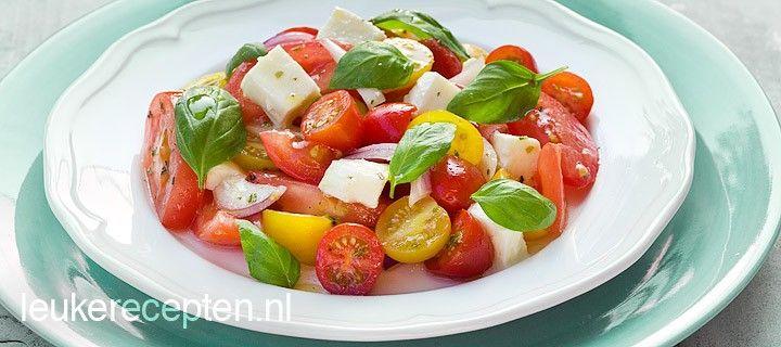 Snelle en lekkere salade met verschillende soorten tomaat, blokjes mozzarella en blaadjes basilicum
