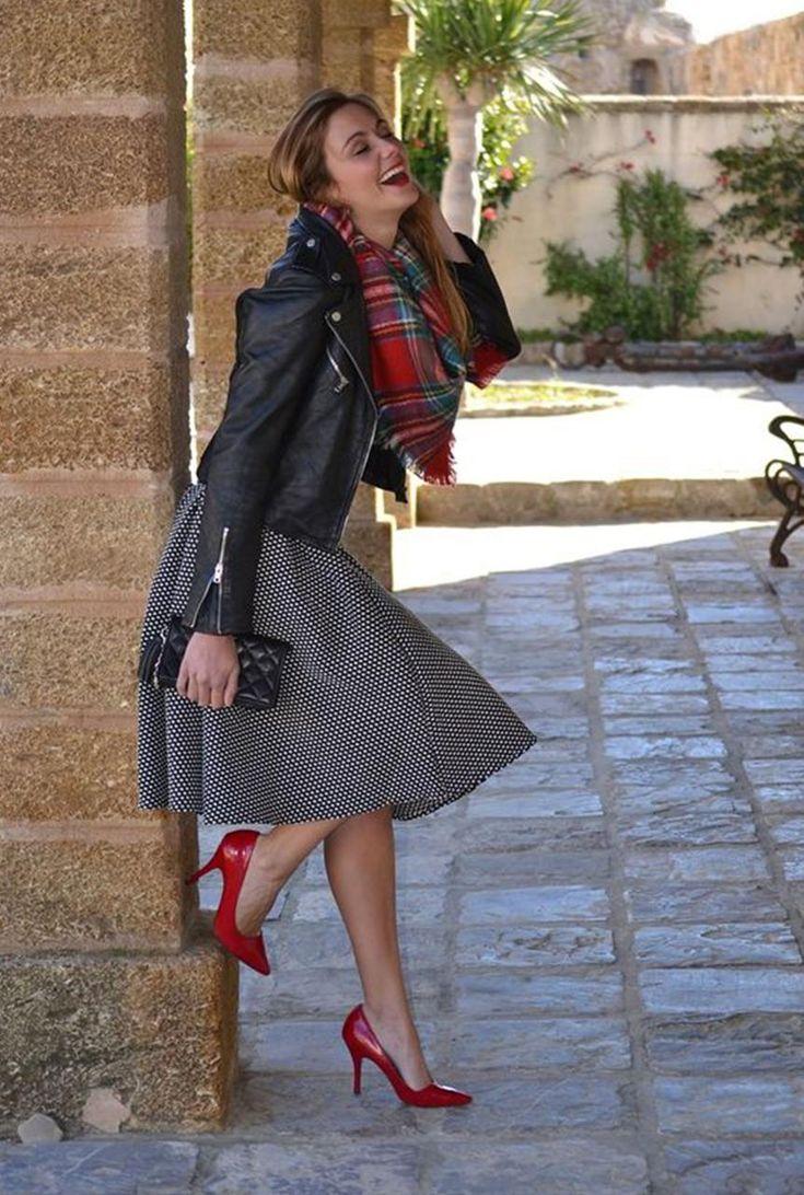 Conjunto chaqueta negra, falda negra estampada, tacones rojos, bandolera negra y bufanda multicolor