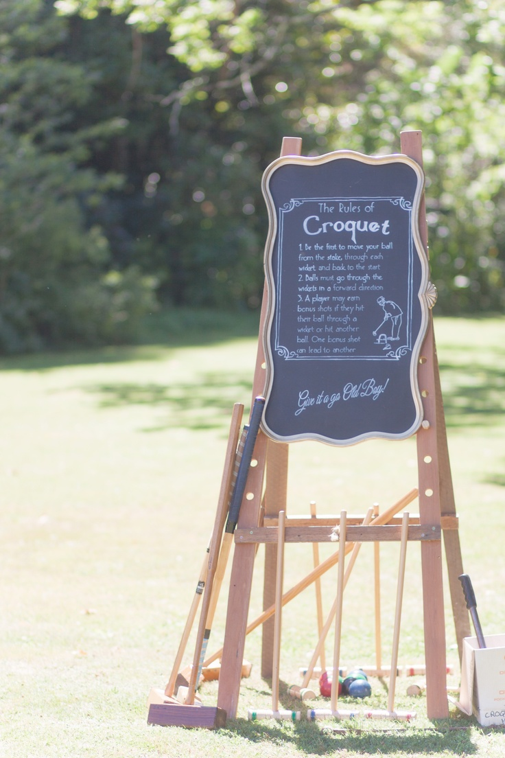 An ornate blackboard was used to explain the rules of croquet.  This was designed & created by Vintage & Pretty.    Photography by Candy Capco