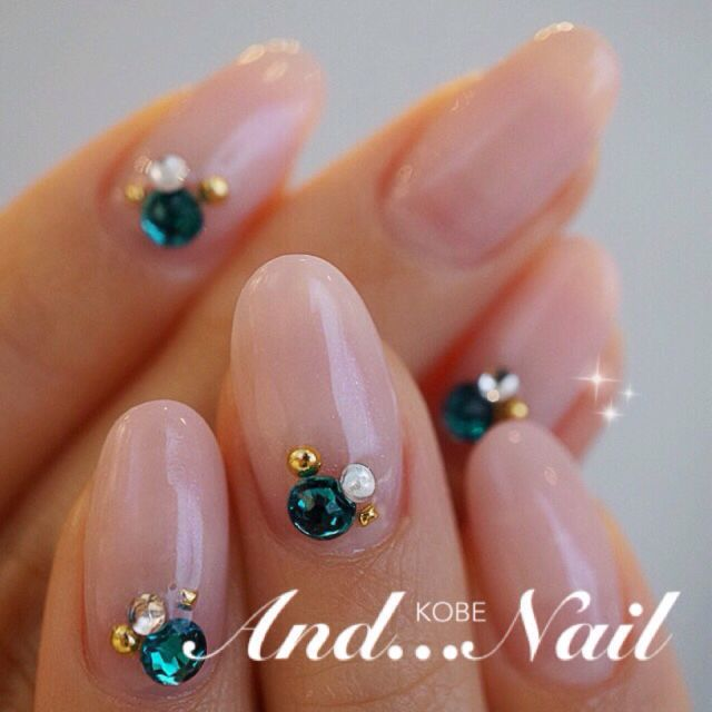 Emerald rhinestones on natural nude pink oval nails