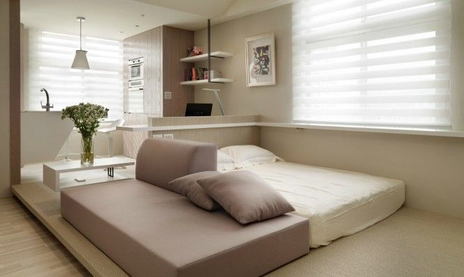 Also kept low-lying is the open-ended sofa, which backs onto the sleeping area. The headboard of the bed is formed by a short wall, to create a clear divide to the home office and kitchen area beyond.