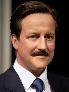 David Cameron PM wears a moustache for Movember. It is hard to tell whether he looks more like Lord Lucan or Basil Fawlty.   David Cameron's image has been transformed by Madame Tussauds with the   simple addition of facial hair to the prime ministerial waxwork.