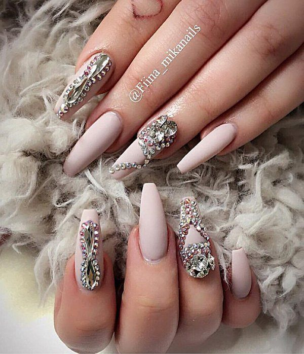 These nails remind me of the Snow Queen. Long, narrow, always modern neutral colors, with lots of rhinestones.