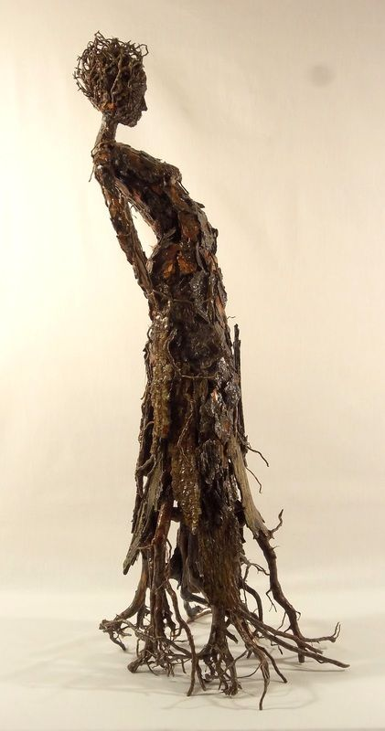 sculpture by Becky Grismer Art.  Roots is part of the series of tree bark figures that are meant to represent some of the individual characteristics shared by trees and humans. Roots represents the common characteristic of both trees and humans having roots. Pine tree roots create the figure's base, head piece and are found in the body detail.