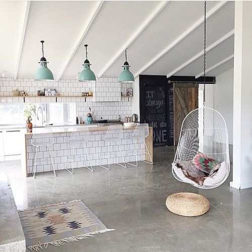 All white kitchen, gray concrete floors, acrylic bar chairs, chalk board, Mediterranean rug, and last but not least... hanging basket chair!
