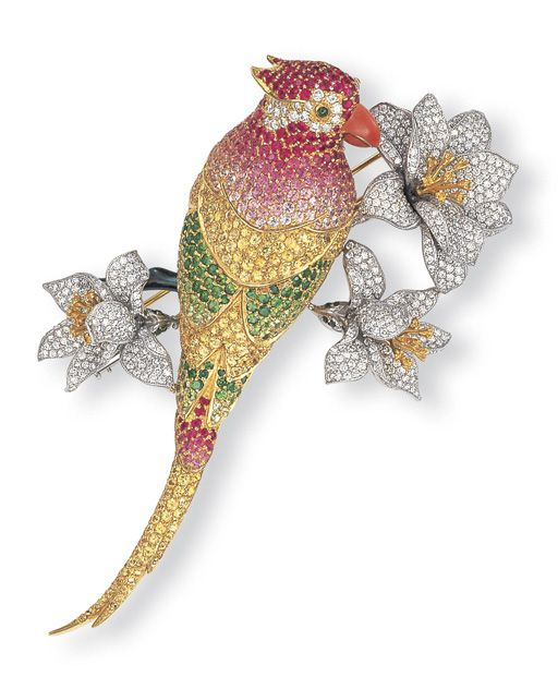 A MULTI-GEM AND DIAMOND PARROT CLIP BROOCH, BY ANGEVIN    Designed as a pavé-set pink and yellow sapphires, tsavorite garnet and diamond parrot, perched on an onyx branch, with three diamond and yellow diamond flowers, mounted in 14k white and yellow gold