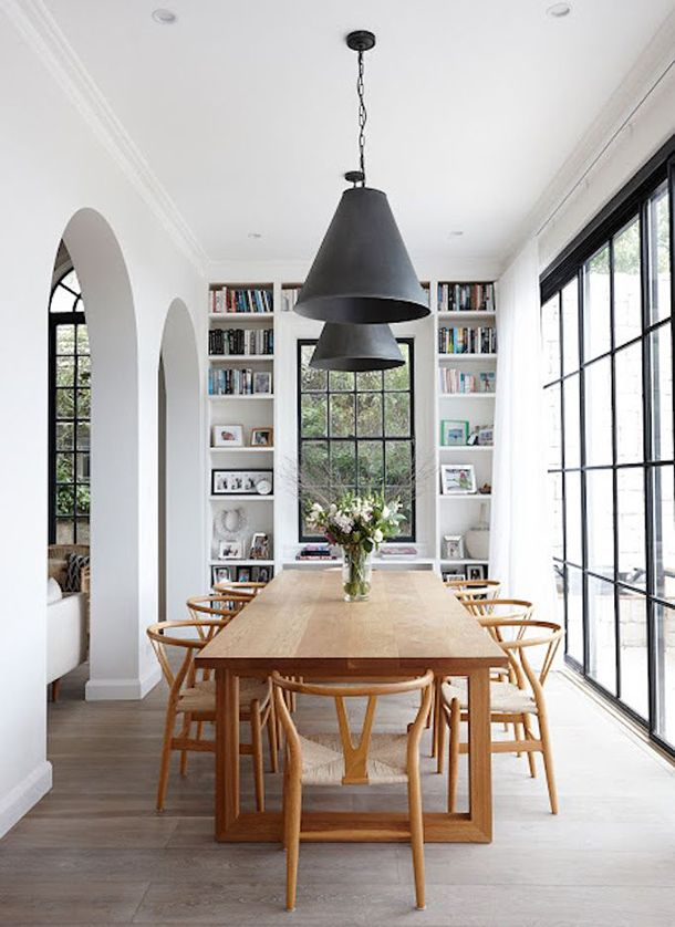 White dining room with large black iron windows and arched doorways.