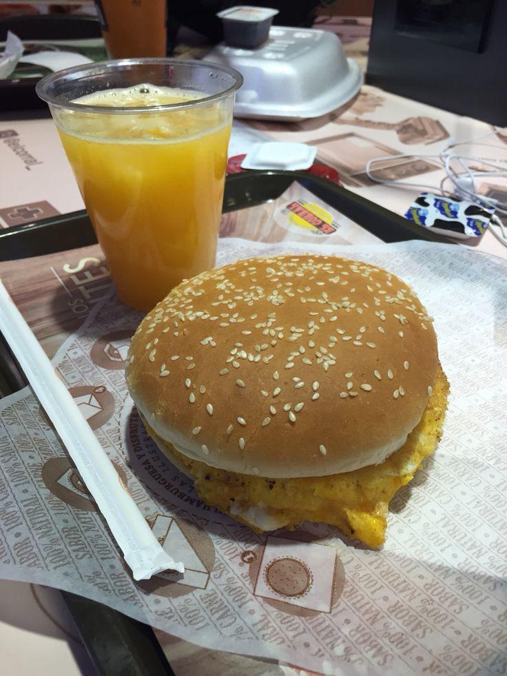 Huevos con salchicha en pan hamburguesa y jugo de Naranja