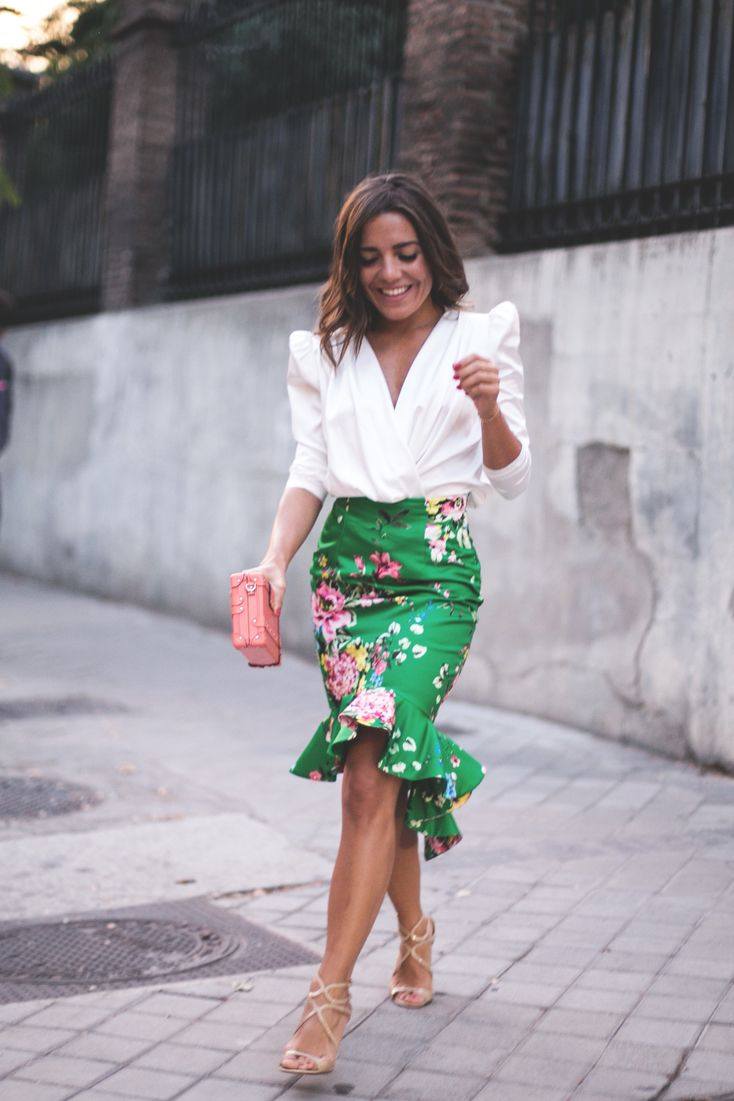 Dramatic outfit with cream blouse, floral ruffle skirt, pink bag, and gold heels. So feminine and sophisticated.